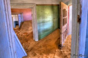Kolmanskop Ghost Town The sands that were once swept up every morning now gather unhindered. The desert encroaches into the buildings, gradually filling the empty rooms with smooth rolling drifts. The houses still stand but it is the elements that are in control. Taken at Kolmanskop Namibia.