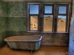 Kolmanskop Ghost town lie in the dry, barren stretches on the edge of the Namib Desert in South-Western Africa. Among the gentle curves of the sand drifts and bleached stone outcrops, ornate buildings rise, defying their desolate surroundings.